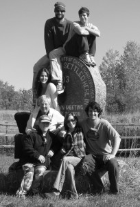 The four founders of Zeno and three friends sitting on a monument  in Lincoln, Vermont, smiling.