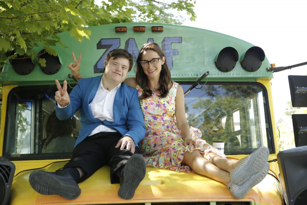 Ila, a white woman with shoulder-length brown hair, smiles at the camera. She's sitting on the hood of the Zeno bus with her arm around a young man with Down Syndrome. Both are wearing 60s-style costumes and holding up peace-signs.
