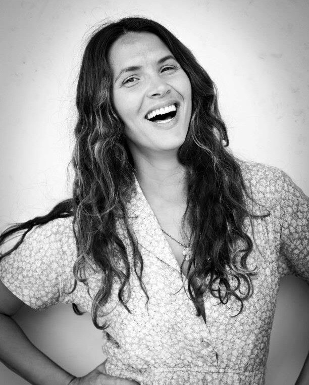 Vanessa, a white woman with long wavy dark hair, smiles at the camera.  She's outside, wearing a floral dress and standing against a wall. The picture is black and white.
