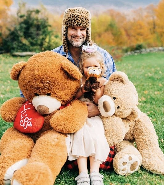 Will, a white man wearing a leopard-print bomber hat, smiles at the camera. He's outside, hugging two giant teddy bears and his young daughter.