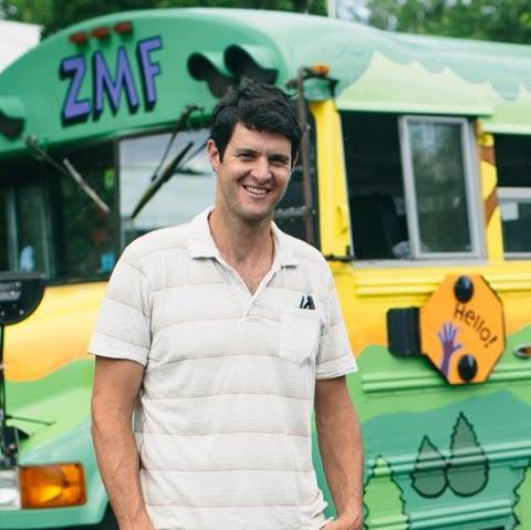 Peter, a white man with short dark hair, smiles at the camera. He stands in front of the Zeno bus, wearing a white striped t-shirt.