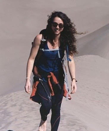 Emily, a white woman with long, dark curly hair, smiles at the camera. She's outside on the sand dunes, wearing hiking gear and a backpack.