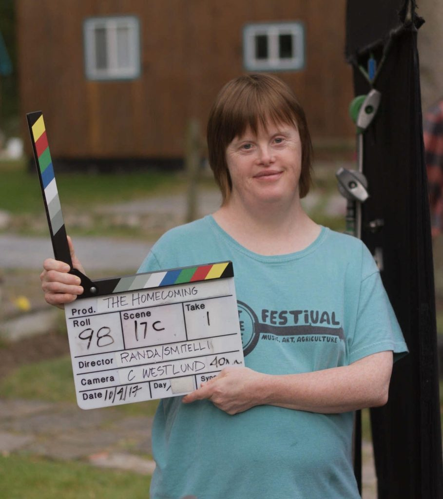 Rachael, a white woman with straight red hair and Down Syndrome, smiles at the camera.  She is outside and holding a clapperboard for the filming of one of Zeno's movies.